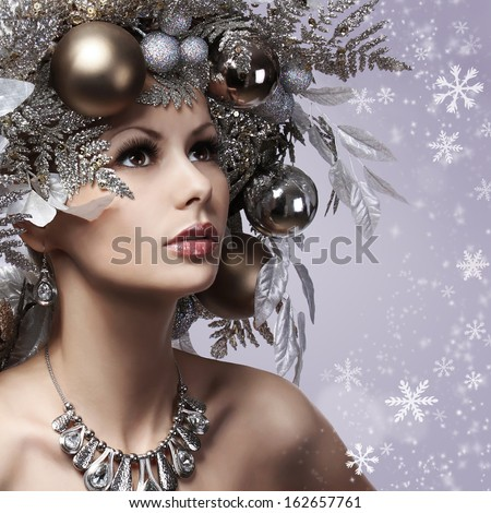 Christmas Woman With New Year Decorated Hairstyle. Snow Queen. Portrait Of Fashion Girl With Silver And Gold Christmas Balls Over Snowflakes Background. Holiday Card