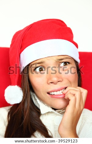 Christmas woman with santa hat nervous biting nails. Beautiful mixed asian / caucasian model.