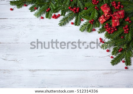 Christmas wooden background with branches of trees, berries and red ribbon