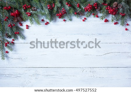 Christmas wooden background with branches of trees, pine cones and red berries #497527552
