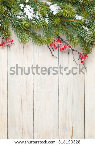 Christmas wooden background with fir tree and holly berry. View from above with copy space #316153328