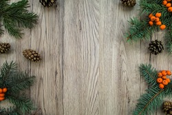 Christmas wooden background with natural decoration: fir tree, cones and rowanberries. Rustic wooden background, view from above. Flat lay, top view
