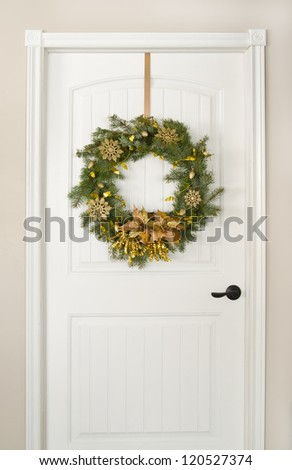 Christmas wreath, decorated in gold on a white door