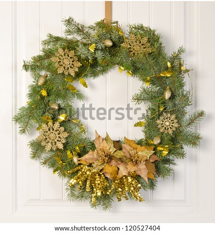 Christmas wreath decorated in gold on a white door