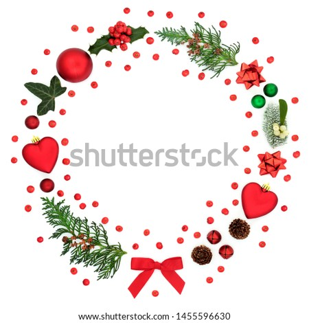 Christmas wreath decoration with loose holly berries, baubles, winter flora and symbols on white background with copy space. Festive concept for the holiday season. #1455596630