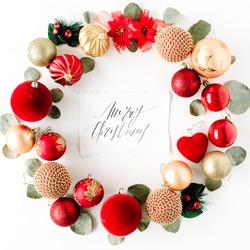 christmas wreath frame made of colored bright christmas balls and calligraphy words merry christmas on white background. flat lay, top view