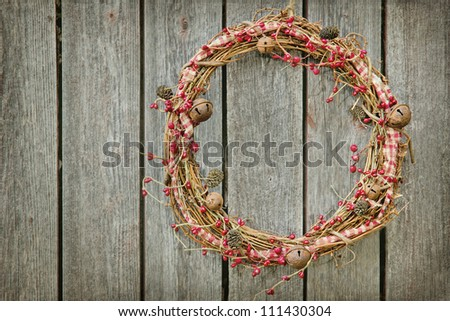 Christmas wreath hanging on a wooden rustic vintage background with copy space