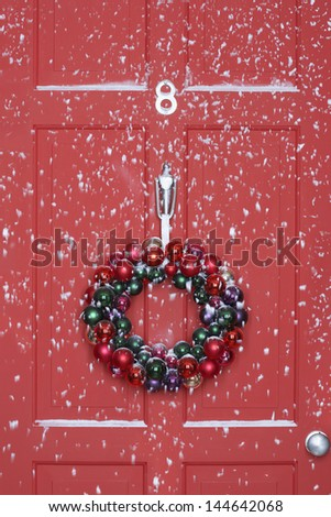 Christmas wreath hanging on door with snowfall