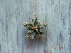 Christmas wreath in a shape of golden geometric star with fir twigs hang on rustic wooden door, traditional Xmas ornament. Minimalist zero waste trendy Xmas decor.
