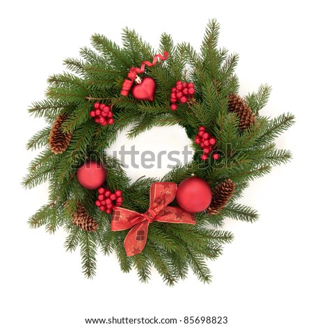 Christmas wreath made of blue spruce fir pine with red bauble decorations, berry clusters, pine cones and bow isolated over white background.