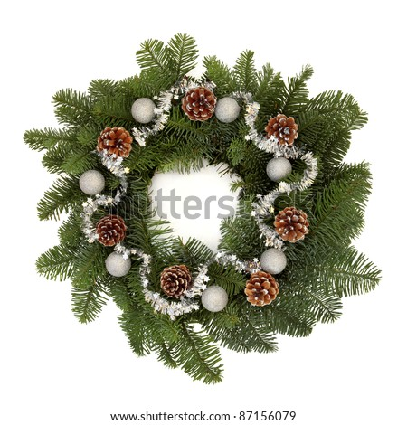 Christmas wreath of blue spruce fir, pine cones with sparkling silver bauble decorations and isolated over white background.