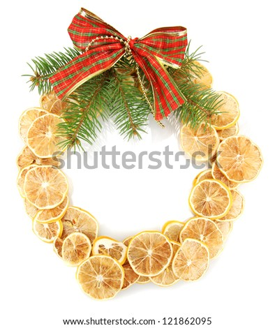 christmas wreath of dried lemons with fir tree and bow isolated on white