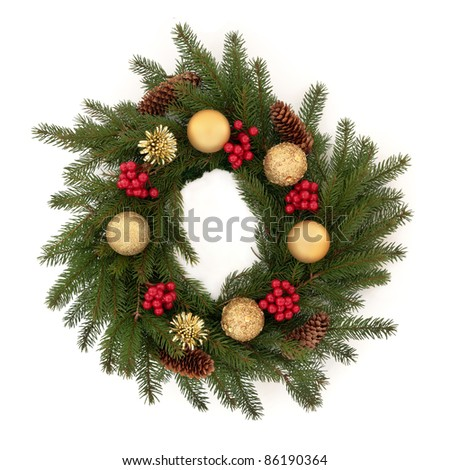 Christmas wreath of pine fir with red holly berry clusters, pine cones and golden bauble decorations isolated over white background.