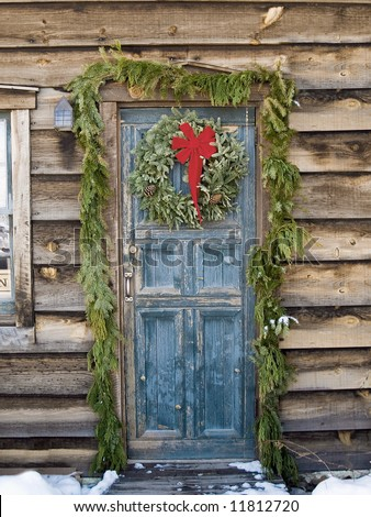 Christmas wreath on a rustic door of a log cabin