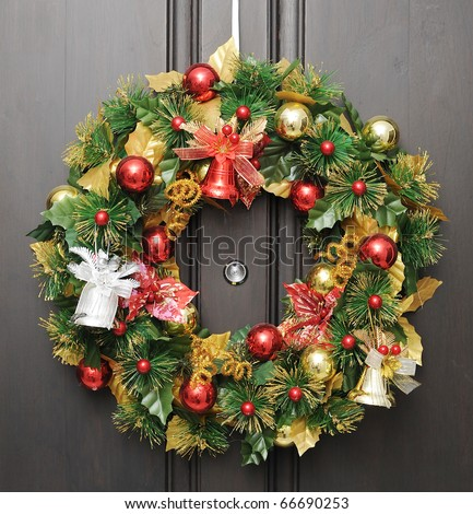 christmas wreath on dark wooden door with peephole in the center