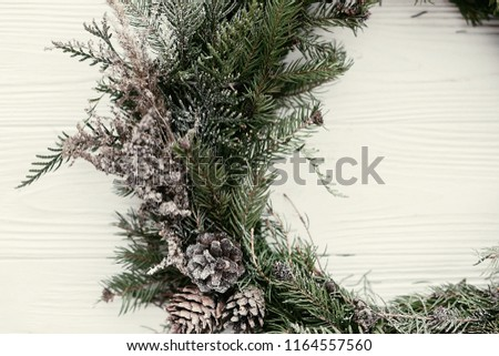 Christmas wreath. stylish rustic christmas wreath on white wooden door with pine cones,fir branches,snow. space for text. handmade decor for winter holidays.