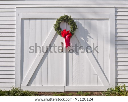 Christmas wreath with a red ribbon, hanging on a white wooden barn's double doors.