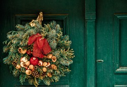 Christmas wreath with fir branches, cones, apples and nuts hangs on a green wooden door. Town house exterior, decorated for Christmas.