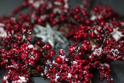 Christmas wreath with frozen red berries covered with snow over dark background, selective focus. Christmas decorations. Winter holidays.