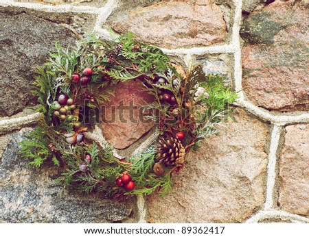 Christmas wreath with natural decorations hanging on a rustic stone wall with copy space.
