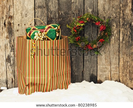 Christmas wreath with natural decorations hanging on a rustic wooden wall beside a colorful bag filled with christmas gifts.
