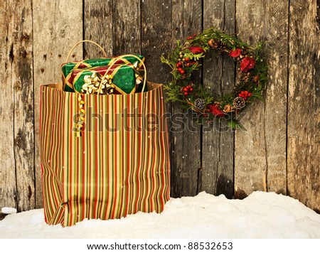 Christmas wreath with natural decorations hanging on a rustic wooden wall beside a colorful bag filled with christmas gifts on a snowy day.