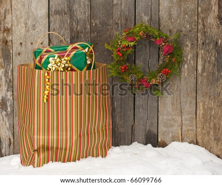 Christmas wreath with natural decorations hanging on a rustic wooden wall with a bag of gifts in the snow.