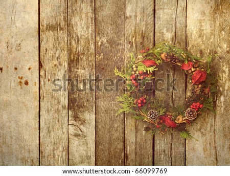 Christmas wreath with natural decorations hanging on a rustic wooden wall with copy space.  Grunge textured.