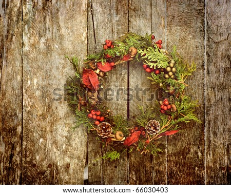 Christmas wreath with natural decorations hanging on a rustic wooden wall with copy space.  Heavily grunge textured.
