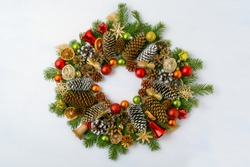 Christmas wreath with pine cones, red and golden ornaments. Christmas background with baubles, jingle bells and dried orange slices