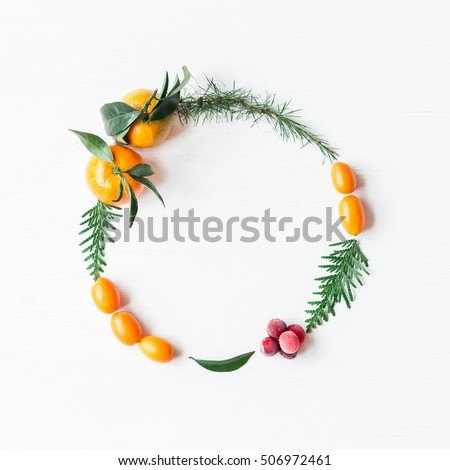 Christmas wreath with tangerines, cranberries, thuja branches, kumquats. Flat lay, top view