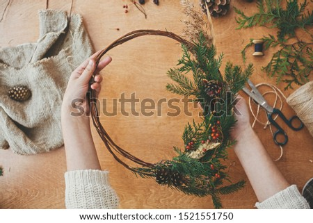 Christmas wreath workshop. Hands holding fir branches, pine cones, berries, thread, scissors on wooden table, flat lay. Making rustic christmas wreath. Authentic rural wreath