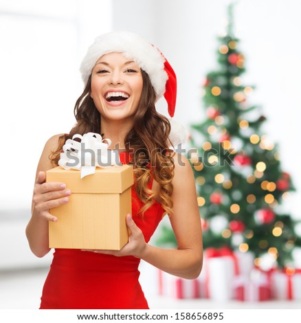 christmas, x-mas, new year, winter, happiness concept - smiling woman in santa helper hat with gift box stock photo
