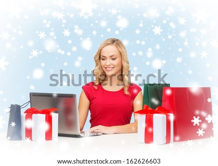 christmas, x-mas, online shopping concept - woman with gift boxes, bags and laptop computer