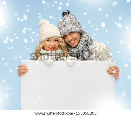 christmas x-mas winter happiness concept family couple in a winter clothes holding blank board