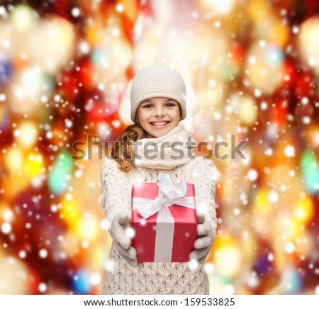 christmas, x-mas, winter, happiness concept - smiling girl in hat, muffler and gloves with gift box