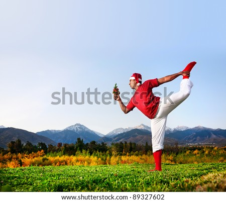 Christmas yoga natarajasana dancer pose by funny Indian man in white trousers, red socks and Christmas hat with looking at Christmas tree at mountain background. Free space for text