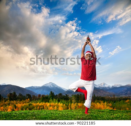 Christmas yoga vrikshasana tree pose by happy Indian man in white trousers, red socks and Christmas hat with Christmas tree at mountain background. Free space for text