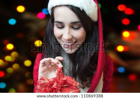 Christmas. Young pretty girl opening christmas present