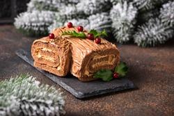 Christmas yule log cake. Traditional chocolate dessert on festive background
