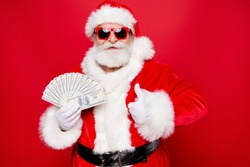 Christmastime currency winter eve wish present gifts. Aged mature grandfather old satisfaction senior in tradition costume headwear spectacles white beard give thumbs up money isolated red background