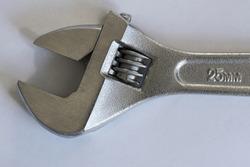 chrome adjustable spanner on light gray background. Diameter 25mm. Worker's tools. Mechanism.