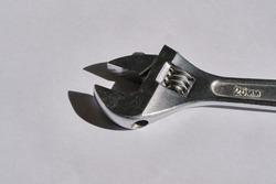 chrome adjustable spanner on light gray background. Diameter 25mm. Worker's tools. Mechanism. Hard lighting