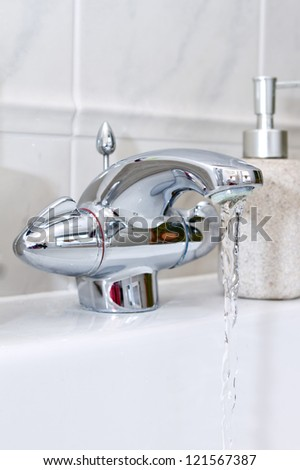 chrome bathroom tap with water running