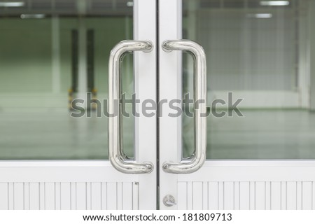 Chrome door handle and glass of aluminium door inside building.