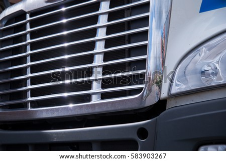Chrome grille bonnet American modern big rig semi truck with a reflection of the surrounding area and the glare of sunlight on the parallel strips of grille.