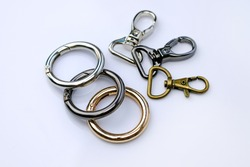 Chrome metal carabiners for a backpack strap. Round carabiner for a woman's bag. Stylish chrome fittings. Bag accessories metal clip buckle. Key ring with clipping path.