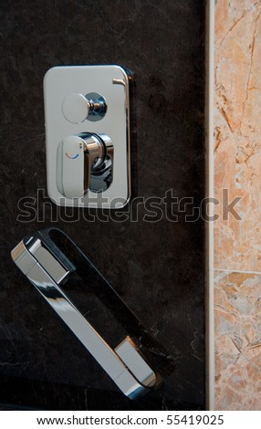 Chrome-plated grab handle and  tap for hot and cold water at the bath marble wall