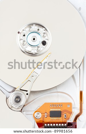 chrome - sliver hard drive with orange circuit board and ribbon. top down closeup view