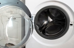 Chromed drum of a washing machine with an open lid.